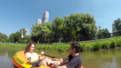 Couple sails in inflatable boat on river with bridges and makes selfie Stock Footage