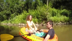 Couple sails in inflatable boat on river, man makes selfie, top view Stock Footage