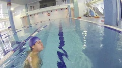 Man in rubber cap swims in indoor pool and makes selfie Stock Footage