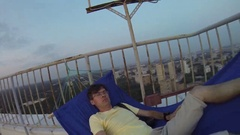 Man lies in hammock on roof of tall building and makes selfie Stock Footage