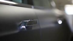 Retract knob of Tesla S car door and female hand. Stock Footage