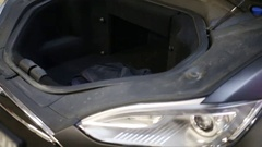 Opened trunk under hood and flashing headlights of modern black car Stock Footage