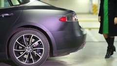 Woman closes trunk and goes away near Tesla S car Stock Footage