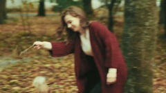 Girl in the autumn park playing with the dog fox terrier Stock Footage