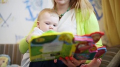 Mother with little cute son read bright book in room Stock Footage