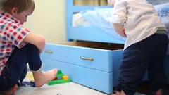 Two little brothers play toys near bed with big drawer in room Stock Footage