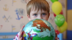 Little boy in shirt holds ball globe in room, shallow dof Stock Footage