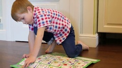 Little boy plays with interactive alphabet on floor in room Stock Footage