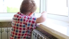 Boy plays with white toy train on windowsill in room Stock Footage