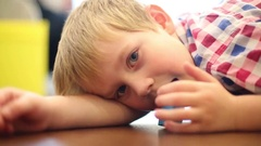 Little boy lies on floor, chews cube and blinks, shallow dof, close up Stock Footage