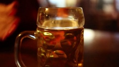 Female hand takes big glass beer mug in cafe, girl out of focus Stock Footage