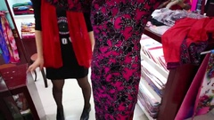 Woman trying on pink dress in Chinese style on big market Stock Footage