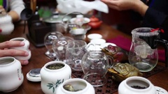 Chinese tea, cups, teapot are on table, hands of people Stock Footage