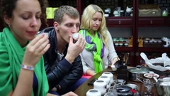 Two women and man taste Chinese tea during tea ceremony Stock Footage