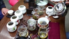 Female hands pour water into teapot during tea ceremony Stock Footage