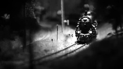Black and white footage of a train model travelling down the railroad Stock Footage