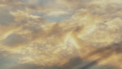 Cloudscape with large, building clouds and sunrise breaking through cloud mass Stock Footage