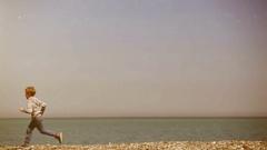 Simple minimalist footage: a kid runs along the seacoast Stock Footage