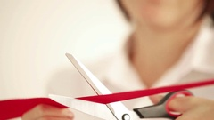 Woman cuts a red tape with scissors ceremonially Stock Footage