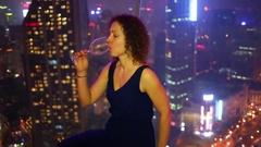 Woman drinks wine near panoramic window, night city behind glass Stock Footage