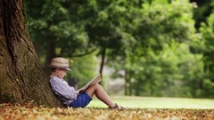 A boy sits under the big linden tree and reads a book Stock Footage