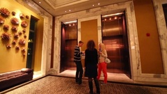 Two woman and man wait lift in hall in IFC Residence hotel Stock Footage