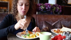 Beautiful woman eat breakfast (boiled corn and croissant) on sofa in hotel Stock Footage
