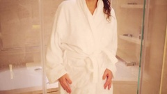 Woman in white bathrobe coming out of bathroom with glass doors Stock Footage