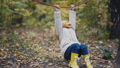 Little girl in yellow boots plays with rope at playground on autumn park Stock Footage