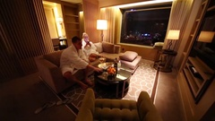 Man and woman in bathrobes sit on couch in hotel room Stock Footage