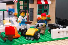 Lego girl with cleaning brush and man with lawnmower in backyard Stock Photos