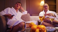 Man and woman in bathrobes on couch, wine, tangerines on table Stock Footage