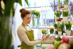 Smiling florist woman making bunch at flower shop Kuvituskuvat