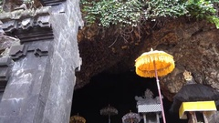 4k Bats flying at entry of bat cave temple Goa Lawah Bali zoom in Stock Footage