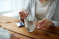 Woman stirring medication in cup with spoon Stock Photos