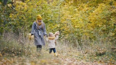 Little daughter with her mommy and Taddy bear walks in autumn park - plays the Stock Footage