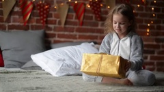 Preteen child girl wake up in her bed dressed in warm xmas pajamas in the Stock Footage