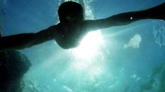 Underwater footage: a man dives and swims away, after a while a fish comes by Stock Footage
