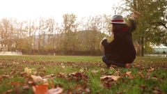 Slow motion footage: master trains her dog, teasing it with a tree leave Stock Footage