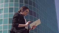 Attractive dark-haired business woman wearing spectacles using her tablet to Stock Footage