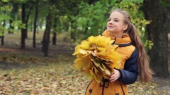 Young girl with a bouquet of spinning leaves in the park Stock Footage