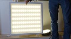 Man presenting LED panel lamp Stock Footage
