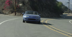 Convertible Driving up Winding Canyon Road Red Epic 5K Stock Footage