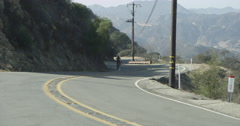 Mountain Biker Riding up Winding Malibu Canyon Road Red Epic 5K Stock Footage