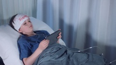 4k Hospital Shot of Injured Child with Breathing Tube Playing on Tablet Stock Footage