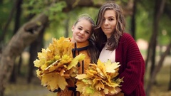 Two sisters hug, with a bunch of leaves in the park Stock Footage