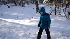 The child tumbles in the snow in the winter park Stock Footage