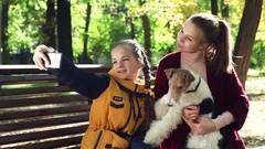 Young attractive girl hugging dog fox terrier, and make selfie smartphone Stock Footage