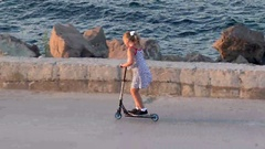 Adorable little girl wearing beautiful dresse riding her scooter Stock Footage