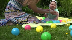 Mother hands put cap on unhappy baby daughter head in outdoor park. 4K Stock Footage